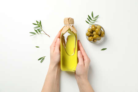 Female hands hold bottle with olive oil on white background, top view
