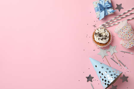 Composition with cupcake and birthday accessories on pink background, space for text