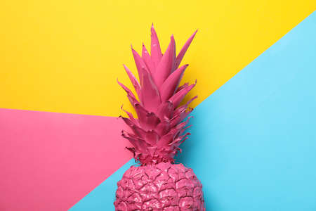 Painted pink pineapple on multicolor background, space for text