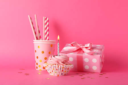 Composition with cupcake and gift box on pink background, space for text
