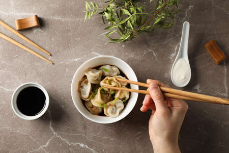Female hand hold dumpling on grey background with bowl of dumplings, top view