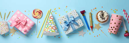 Gift boxes and birthday accessories on blue background, top view