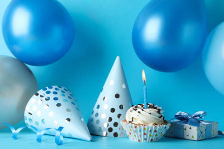 Balloons, birthday hats, cupcake and gift box on blue background, close up Stock Photo