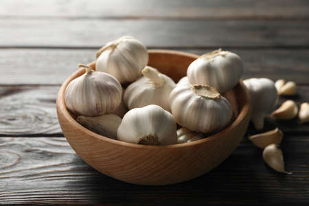 Wooden bowl of fresh garlic bulbs, slices on wooden background, top view. Closeup