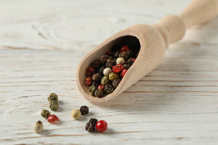 Scoop with different peppercorns on wooden rustic background, close up
