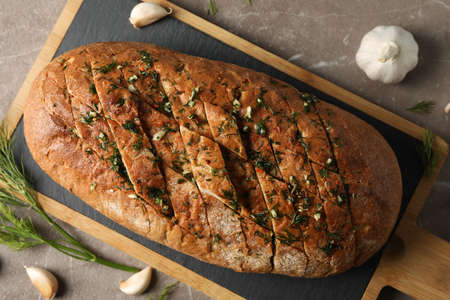 Board with garlic bread and spices on grey background, top view