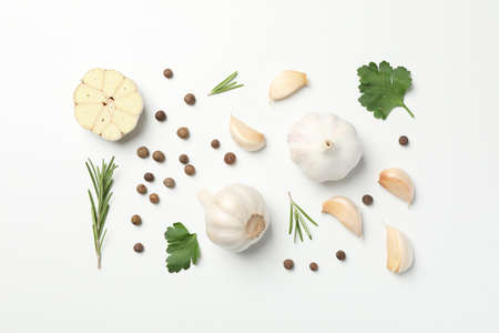 Flat lay of composition, garlic bulbs, slices, spice, parsley, rosemary on white background, top view. Space for text