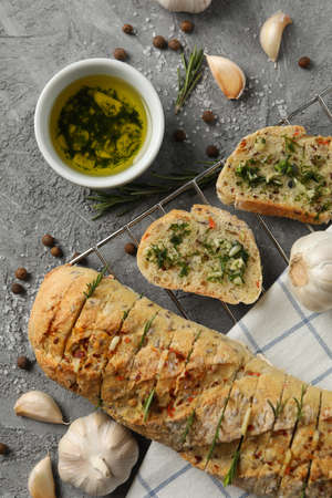 Tasty garlic bread and spices on grey background, top view