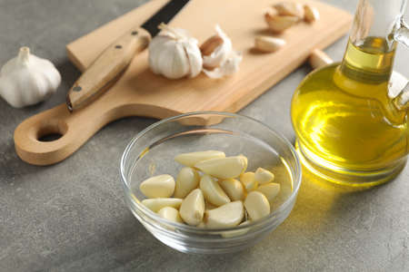 Bowl of garlic slices, bulbs, oil, knife, board on grey wooden background. Closeup