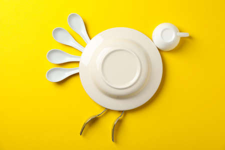 Bird made of plate and cutlery on yellow background, top view