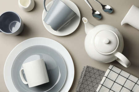 Table setting with teapot on grey background, top view
