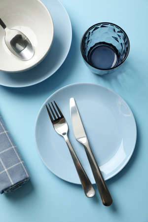 Tableware and cutlery on blue background, top view