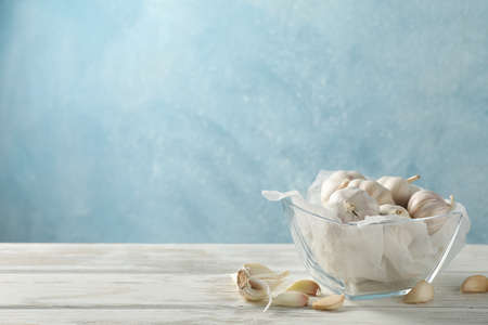 Glass bowl of fresh garlic bulbs, slices on white table against blue background. Space for text