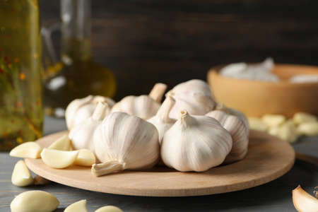 Plate of garlic bulbs, slices, oil on grey table against wooden background, space for text. Closeup