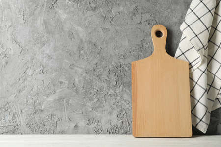 Wooden board on white table against gray background, space for text Zdjęcie Seryjne