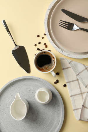 Table setting with cup of coffee on beige background, top view Zdjęcie Seryjne