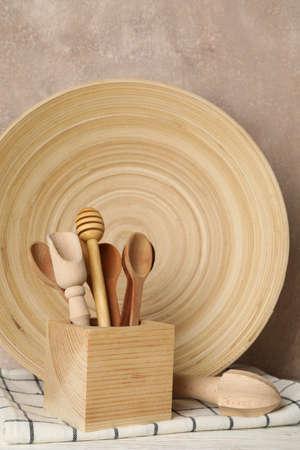 Vaisselle et couverts en bois sur table blanche sur fond marron, espace pour le texte. Fermer