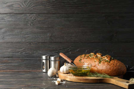 Board with garlic bread and oil on wooden background, space for text Stok Fotoğraf