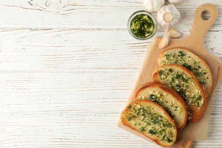 Board with garlic bread on white wooden background, top view