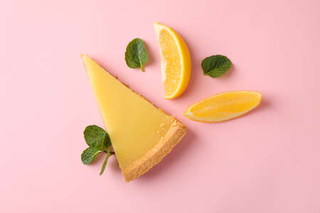 Lemon tart slice and lemon slices on pink background, top view