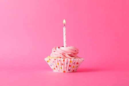 Babeczka ze świecą na różowym tle, miejsce na tekst Zdjęcie Seryjne