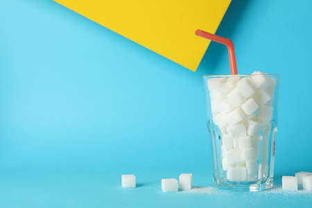 Glass with sugar cubes and straw on two tone background, space for text