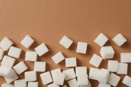 Sugar cubes on brown background, space for text