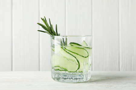 Glass with infused cucumber water on wooden background, close up