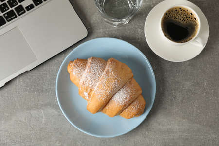 Composition with croissant and computer on grey background, top view