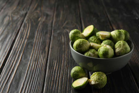 Bowl with brussels sprout on wooden background, space for text