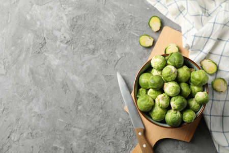 Composition with bowl of brussels sprout on grey background, top view 版權商用圖片
