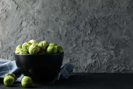 Bowl of brussels sprout on dark background, space for text