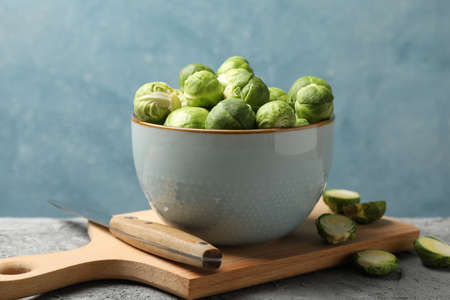 Composition with bowl of brussels sprout on grey table, close up