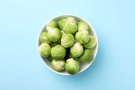 Bowl with brussels sprout on blue background, top view