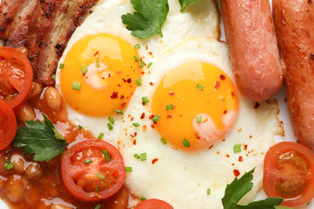 Fried eggs with sausages, vegetables and spices on whole background, close up Stock Photo