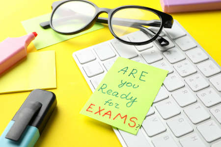 Inscription Are you ready for exams?, keyboard and stationary on yellow background, close up