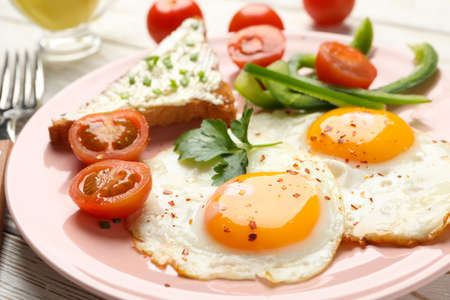 Delicious breakfast or lunch with fried eggs on wooden background, close up Stock Photo