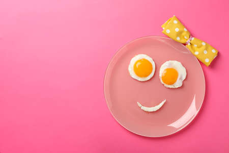 Smile face made of plate with fried eggs on pink background, top view