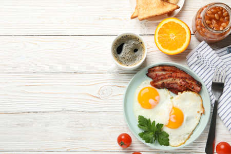 Delicious breakfast or lunch with fried eggs on white wooden background, top view