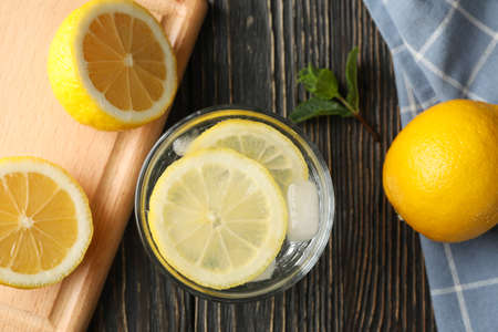 Glass with lemonade and ingredients on wooden background, top view
