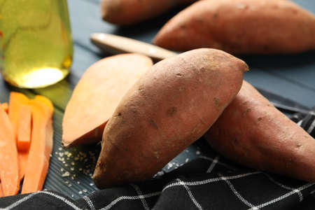 Sweet potato and ingredients on wooden background, close up