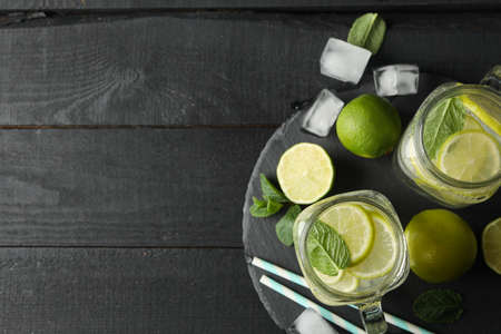 Glass jars with lemonade on dark wooden background, top view Stock Photo