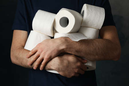 Man holds rolls of toilet paper, front view