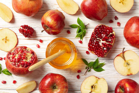Apples, pomegranate and honey on wooden background, top view