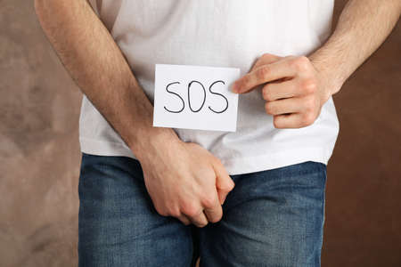 Man holds his crotch and inscription Sos on brown background, close up Stockfoto