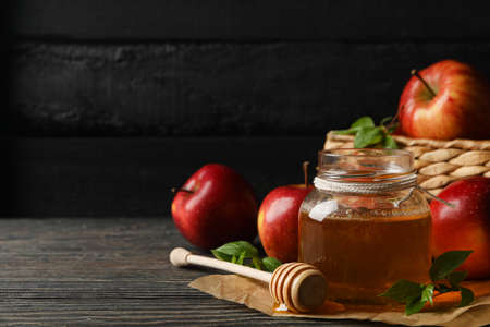Apples and honey on wooden background, space for text