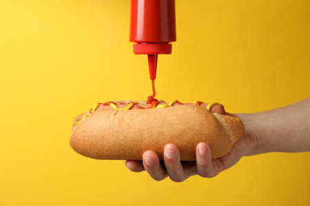 Person pouring ketchup on hot dog, on yellow background Archivio Fotografico