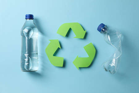 Eco concept with recycling symbol and bottles on blue background Foto de archivo