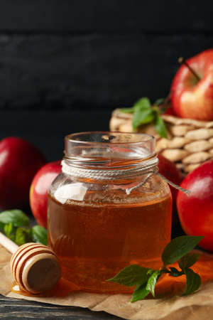 Apples and honey on wooden background, close up