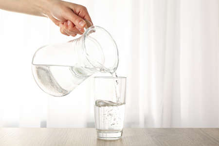 Pouring purified fresh water from the jug in glass on wooden table